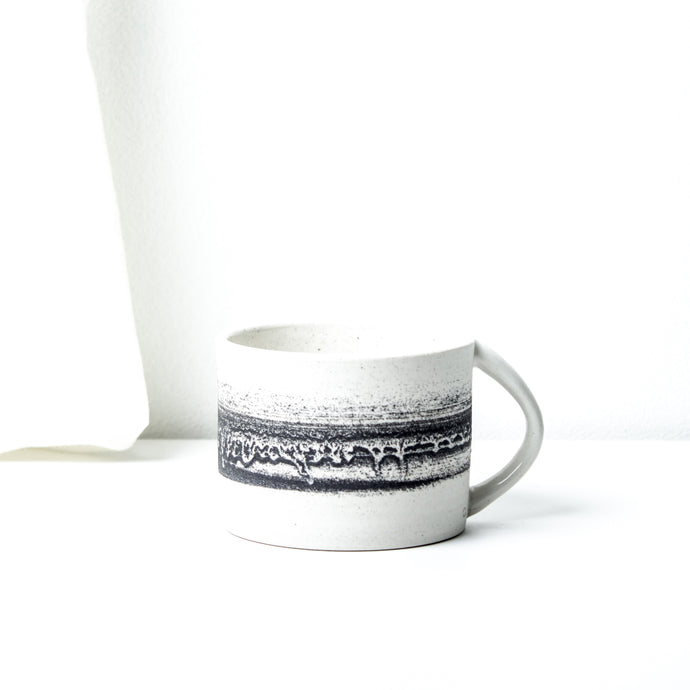 -Latte / Cappuccino Cup -Clear glaze on white porcelain clay -Straight edged, low and wide opening with lip to bottom arch handle -Modern simple shape + natural texture *Basalt Collection Drawing of mixture of dark minerals. The unique organic drawing is applied in a rotation motion of my wheel.