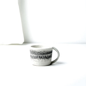 -Espresso Coffee Cup -Clear glaze on white porcelain clay -Slight angle toward opening with lip to foot, full arch handle -Modern simple shape + natural texture *Basalt Collection Drawing of mixture of dark minerals. The unique organic drawing is applied in a rotation motion of my wheel.