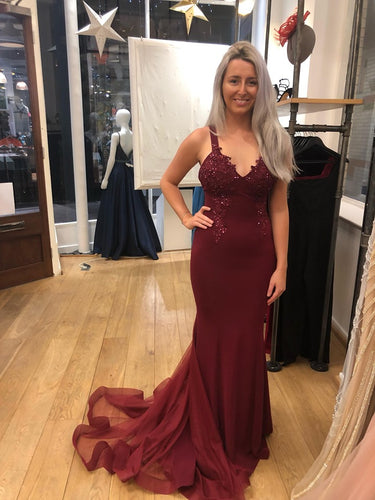 Deep wine burgundy prom and evening gown designed by Pia Michi. Figure flattering. Ideal for an hour glass shape. This dress has beautiful lace detail on the bodice floating down to the hips. Fishtail effect with full tulle train. Low eye catching back.