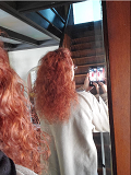 ONC NaturalColors 7RN Irish Red Hair Dye With Organic Ingredients 120 mL / 4 fl. oz. LA  product review. Model is standing with her back to the mirror photographing the mirror image of her newly colored hair over her shoulder - Thumbnail