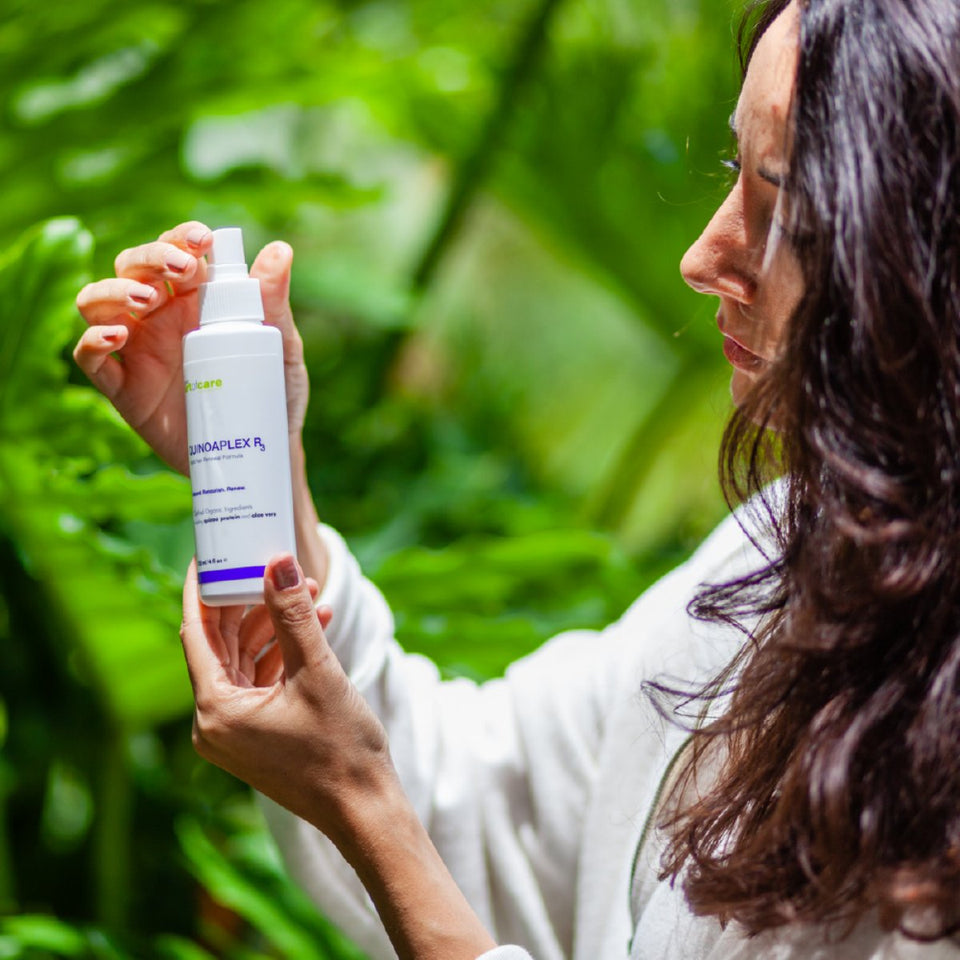 Woman looking at a plastic bottle of ONC artofcare QUINOAPLEX R3 Rapid Hair Renewal Formula 125 mL / 4 fl.oz. she is holding out in front of her