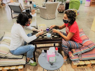 Two ladies sitting in low sitting and doing craftwork on glass-top of chess table