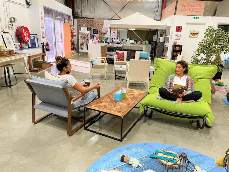 Two ladies sitting on comfortable sofa chairs, talking and smiling