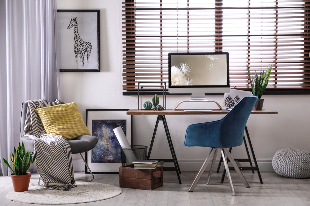 Comfortable workplace near window with horizontal blinds