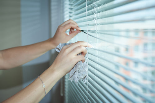 Hand of young woman cleaning blinds