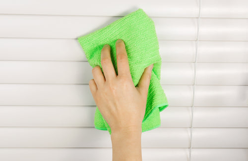 Horizontal photo of female hand cleaning blinds