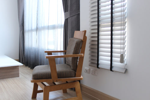 empty chair in front of grey blinds