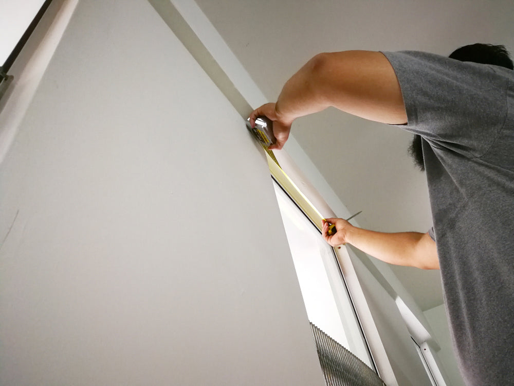 a person installing modern blinds