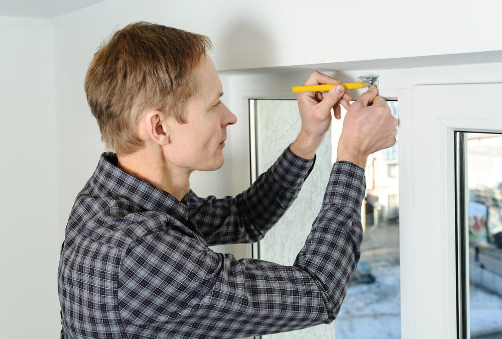 man at window installing blinds