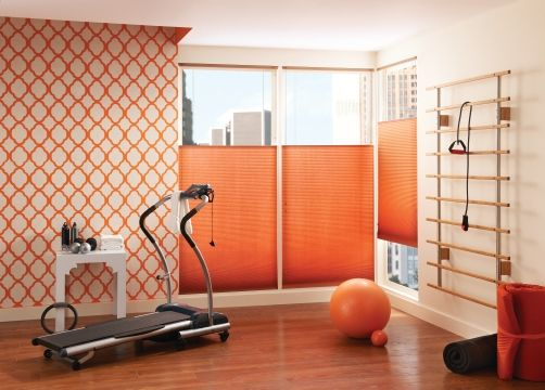 Image of pumpkin colored cellular shades in workout room.