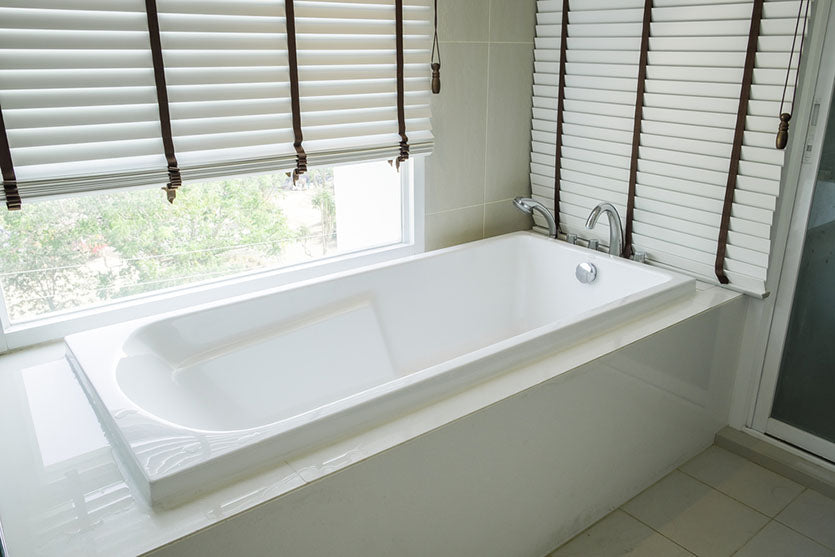 white ceramic tub surrounded by windows