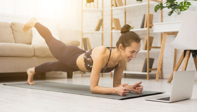 woman doing plank exercise before laptop