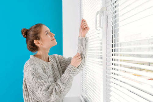 young girl opening blinds at home