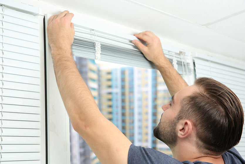 young man installing blinds