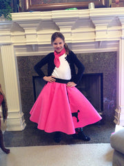 Girl in front of fireplace wearing Pookey Snoo child bubblegum pink poodle skirt and matching scarf
