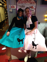 Women at sock hop in Pookey Snoo adult turquoise poodle skirt and adult light pink poodle skirt
