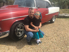Girl in Pookey Snoo child turquoise poodle skirt with dad in front of red 1950s car
