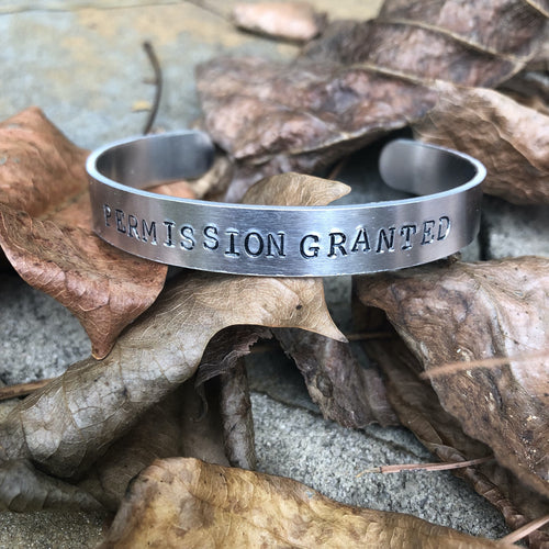 aluminum bracelet with permission granted hand stamped on it.