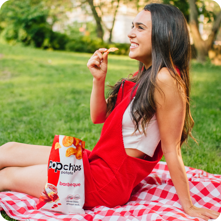 brown haired woman sitting in a park laughing and eating barbeque popchips