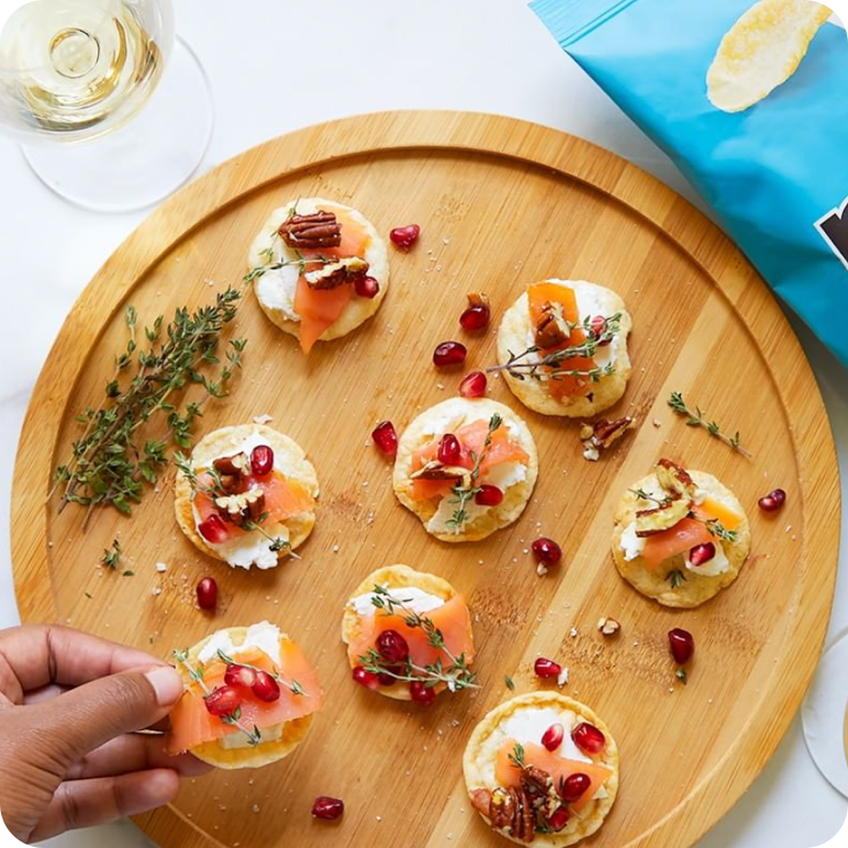 salmon, cream cheese and pomegranate crostini on a sea salt popchi[