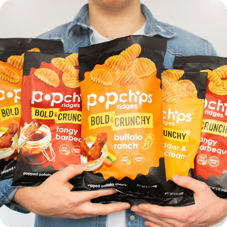 multiple bags of ridgees popchips being held in the arms of a man