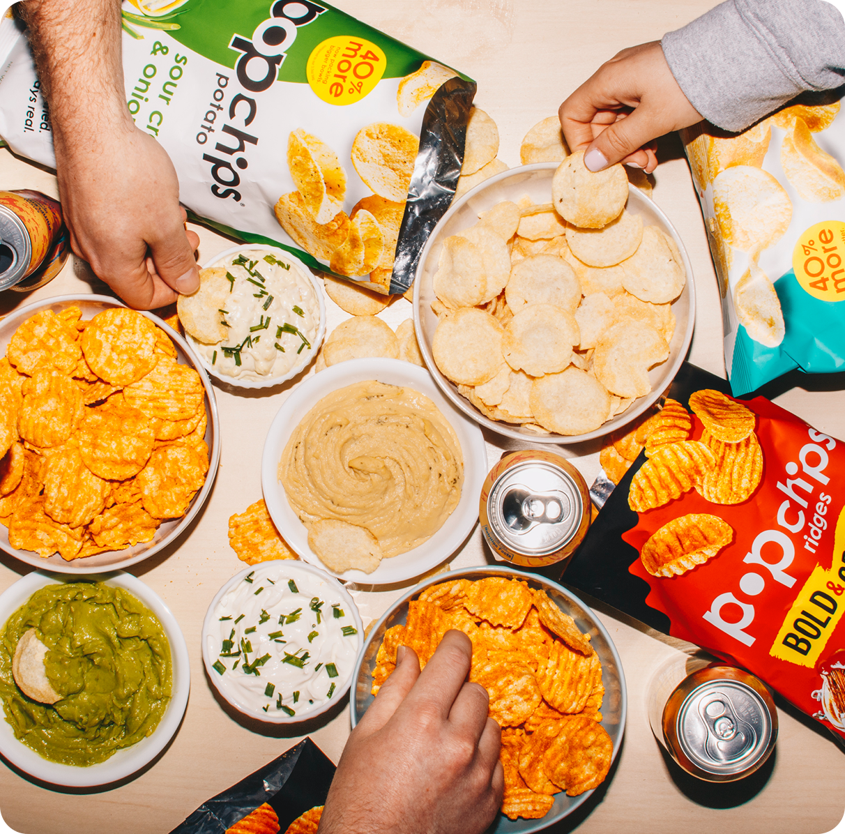 multiple popchips bags with bowls of dip and soda cans on a table