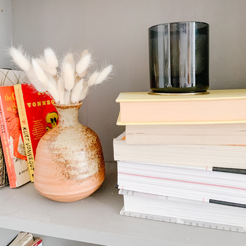 slow living habit declutter, organized bookshelf with bunny tails