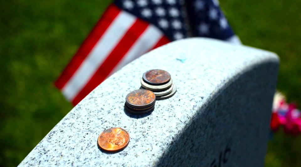 What do coins on a veteran's grave mean?