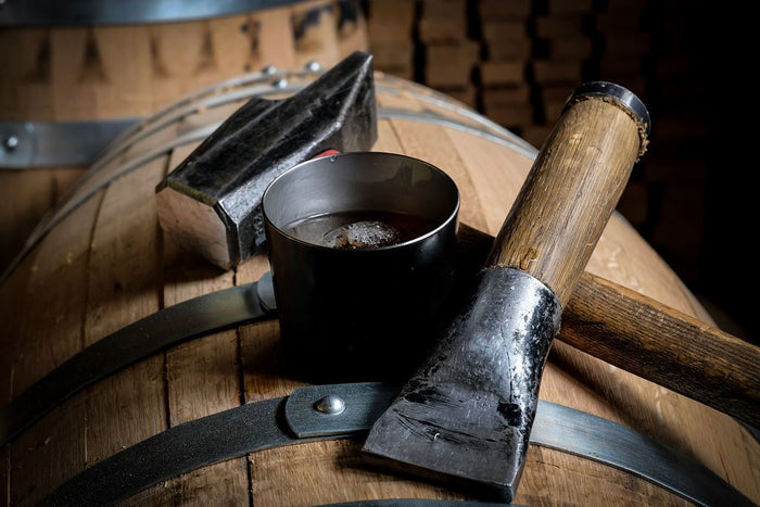 THE DOM original tin cup whiskey glass tumbler on top of a bourbon barrel with hand tools