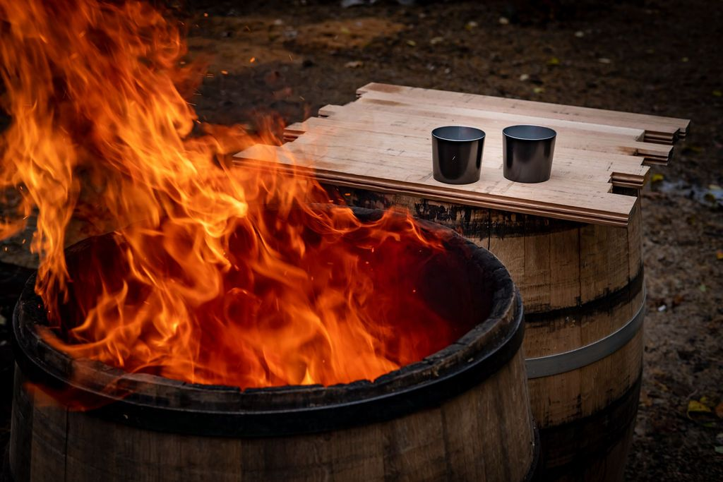 THE DOM original tin cup whiskey glass tumbler on top of a bourbon barrel with fire in the background