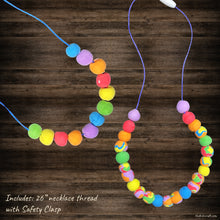 Load image into Gallery viewer, This picture shows The Kids Craft's Cherish the Rainbow Craft Kit - Rainbow Necklace that your kid will be able to create once they are done. Let your kid be a creator with this Craft Kit Box - The Kids Craft, a Creativeana LLC company creation. Your kid will love The Kids Craft's Cherish The Rainbow Crafts as they create their own hot air balloon, decorate their rainbow, create a bracelet, and create their art masterpiece.