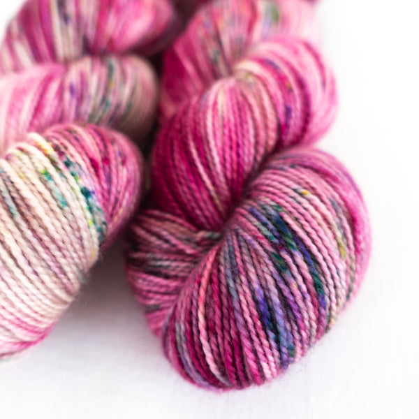 Blossom is hand dyed sock yarn with varying shades of pink and light speckles of teal, yellow and aqua