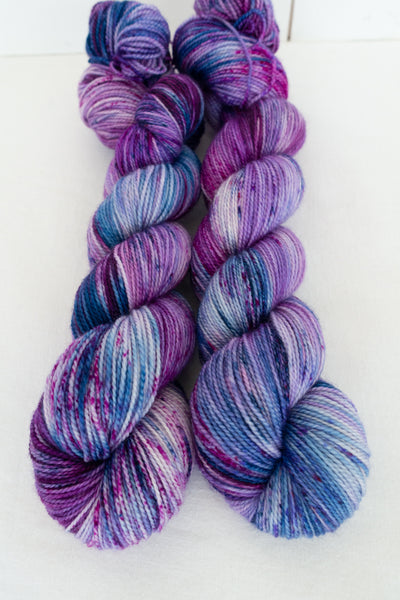Two skeins of hand dyed yarn in shades of purple, pink and blue