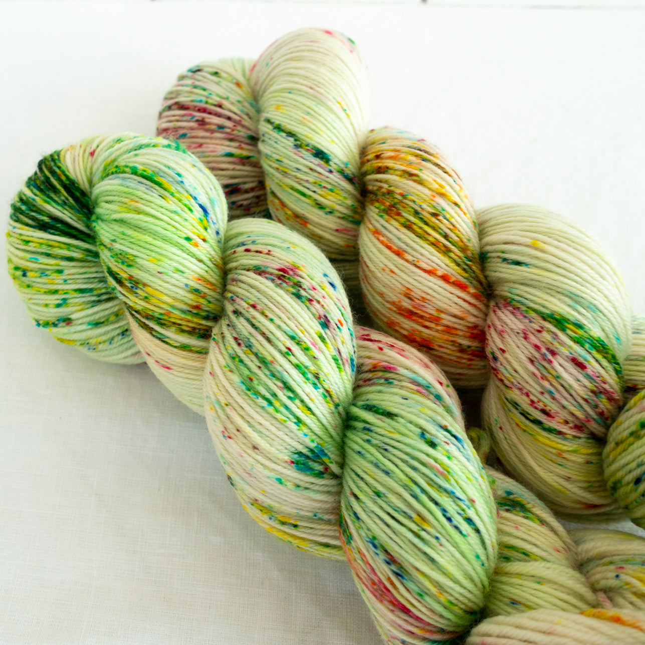 Skip Rope Yarn Co hand dyed sock yarn - two skeins of light green yarn with speckles of green, yellow and pink
