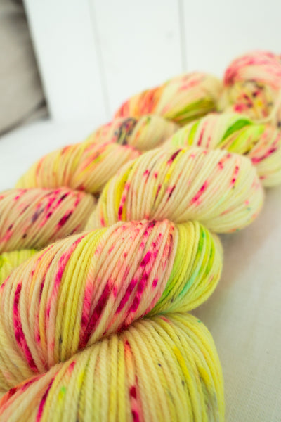 Skip Rope Yarn Co hand dyed yarn - two skeins of bright yellow and pink speckled yarn (close up)