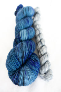 Skip Rope Yarn Co sock set - one full size skein of yarn in a blue shade with a 20 gram mini-skein in light grey on a white background