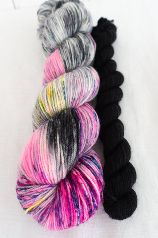 Skip Rope Yarn Co sock set - one full size skein of speckled pink, black and purple yarn with a 20 gram mini-skein in black on a white background