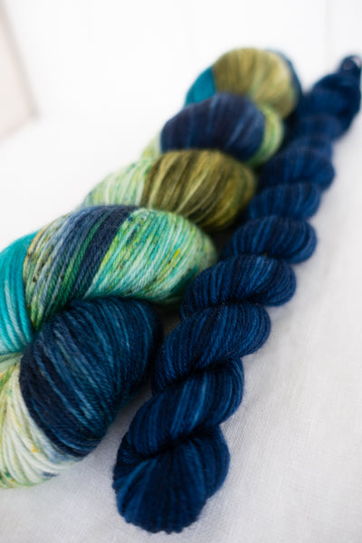 Skip Rope Yarn Co sock set - one 100g skein of speckled yarn in blue, green and olive with a 20 gram mini-skein in dark blue on a white background