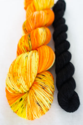 Skip Rope Yarn Co sock set - one full size skein of yarn in a orange/yellow shades with a 20 gram mini-skein in black on a white background