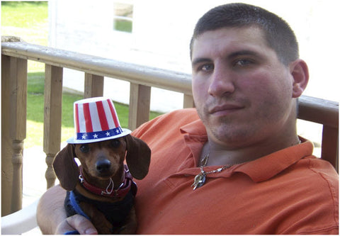 Anthony Paulis - white man with brown hair wearing a short sleeve shirt holding a dog wearing an American themed tophat.