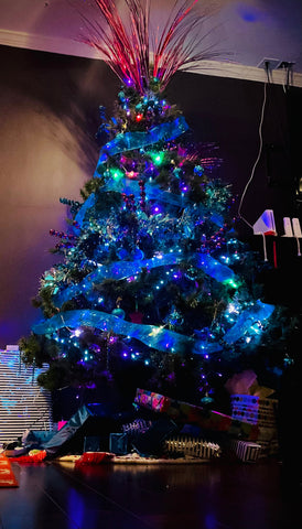 Pine tree decorated with blue and purple lights in Rose Morris's home
