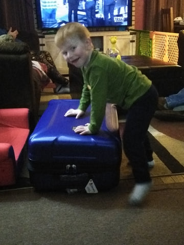 Noah on top of his Safety Sleeper hard shell suitcase