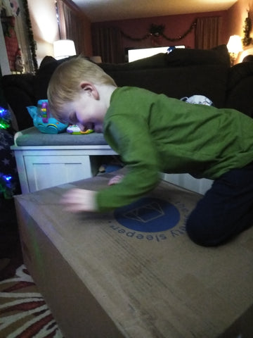 Noah on top of his Safety Sleeper box after it was delivered to his house