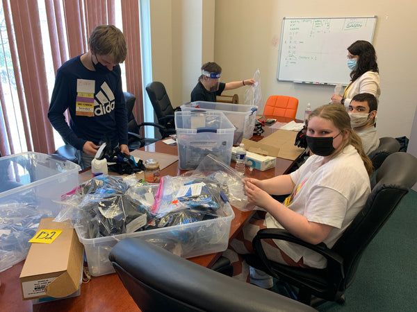 Students from Pine Richland visit Abram's Nation for a day of work study training. In this photo, they sit and stand around a conference table and sort through masks and zippers for stock.