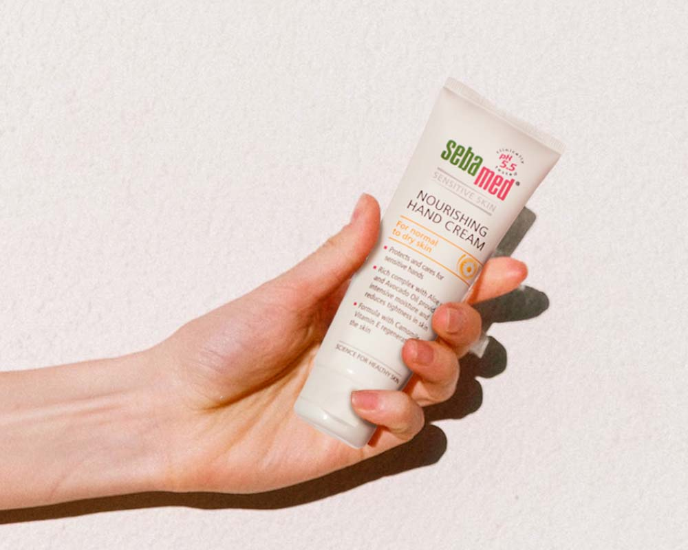 Ladies hand holding a tube of Sebamed Hand Cream