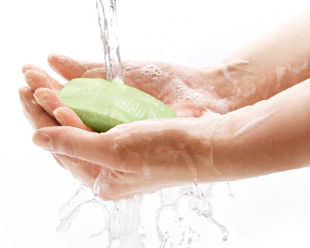 ladies hands with green soap bar under running water