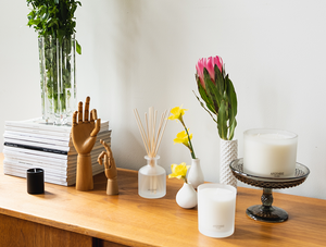 Apotheke white vetiver signature candle with matte candle holder on a wooden table with a candle on a platform behind it, vases with yellow and pink flowers to its left with a diffuser and two wooden hands articulated in different poses.