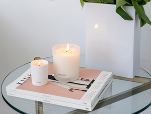 Apotheke white vetiver signature candle with matte candle holder  next to a smaller white and opaque candle holder on a glass table with two photo books below them.