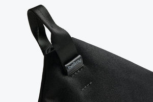 Bellroy Standing Pouch in Melbourne Black with a black leather handle placed diagonally on the top left of the pouch. The photo is zoomed in on the handle and small bellroy leather label.