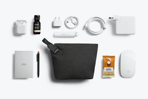 Bellroy Standing Pouch in Melbourne Black with a black leather handle placed diagonally on the top left of the pouch. Around the pouch are all of the potential items to fit inside of the pouch.